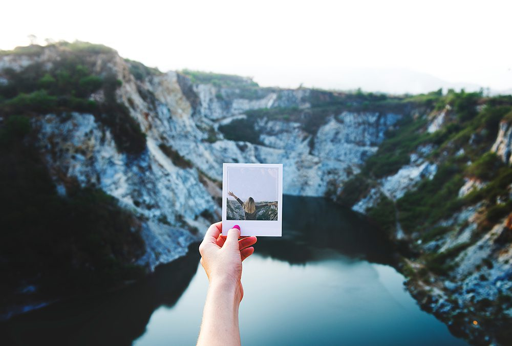 Holding a polaroid picture.